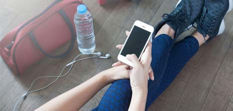 Stock image of a woman's legs and phone at the gym. Also shows gym bag, headphones and water bottle.