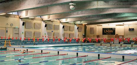 Image of the UNSW Fitness and Aquatic Centre Pool with lanes split in half to show 25m pool. UNSW sign in background and red bunting across pool.
